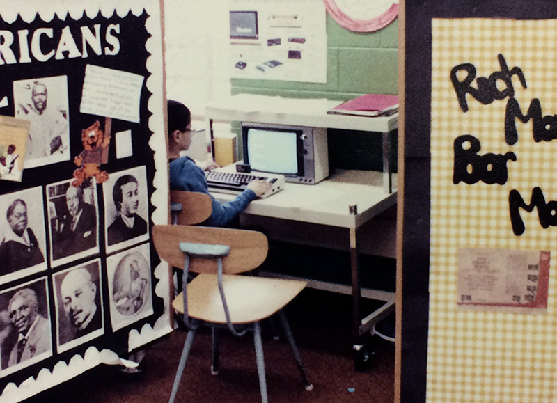 Color photograph of a student using a small personal computer. The keyboard is much thicker than keyboards today and has a cartridge slot at the top. The monitor is a small CRT screen. The student is working at a small desk behind several movable classroom storage units that also served as classroom partitions.