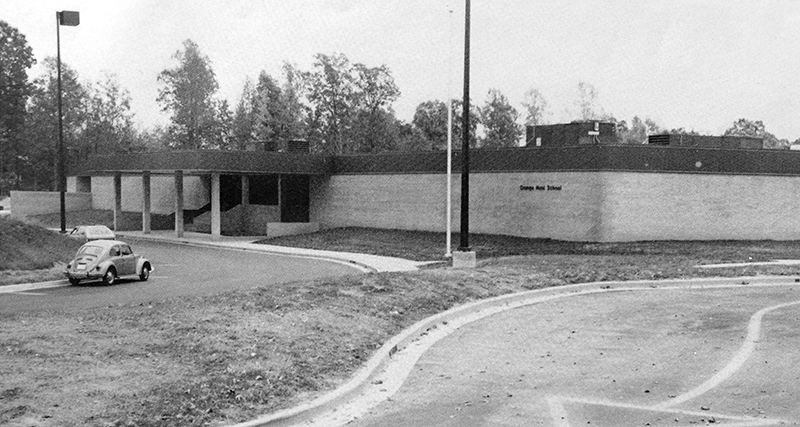 Black and white photograph from Orange Hunt's first yearbook showing the front of the building. The school grounds have been sodded, but no other plants are visible. A Volkswagen Beetle is parked in front of the school.