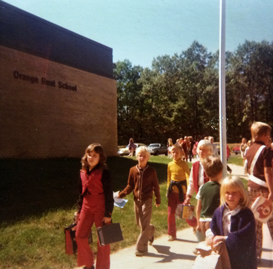 Color photograph taken on September 30, 1974. Students are walking along the sidewalk from the parking lot toward the main entrance. They are carrying backpacks and are wearing earth-toned sweaters or light jackets. The trees in the distance are still green.