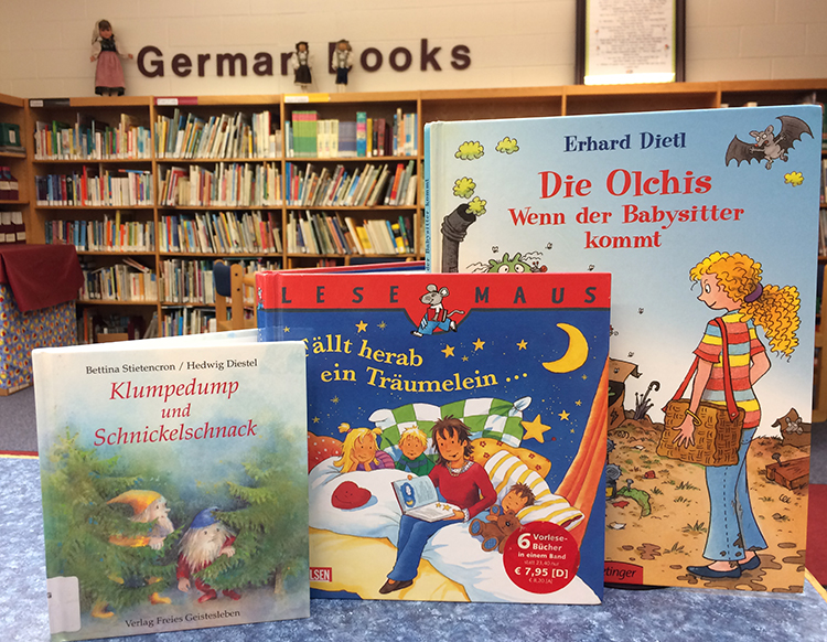 Color photograph taken in the library at Orange Hunt Elementary showing three German-language books. In the distance the German Books section of the library can be seen. The shelves hold hundreds of books.