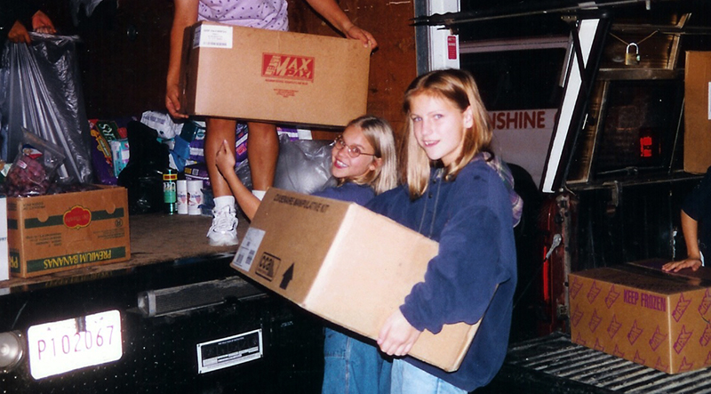 Color photograph of two students who are assisting with loading boxes into the back of a U-haul-style truck as part of a hurricane relief effort. Some of the boxes contain food, clothing, household supplies, and cleaning products.
