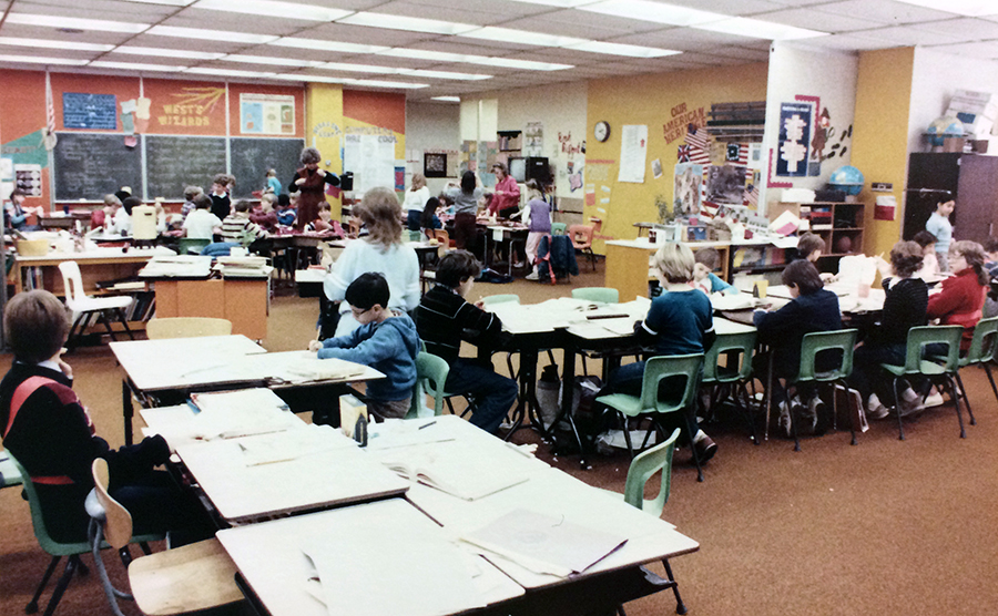 Color photograph of one of the open classrooms at Orange Hunt Elementary School. Individual desks have been clustered together in several groupings. The students in the foreground are working on one lesson, and in the distance a separate group of students are working on a different lesson.
