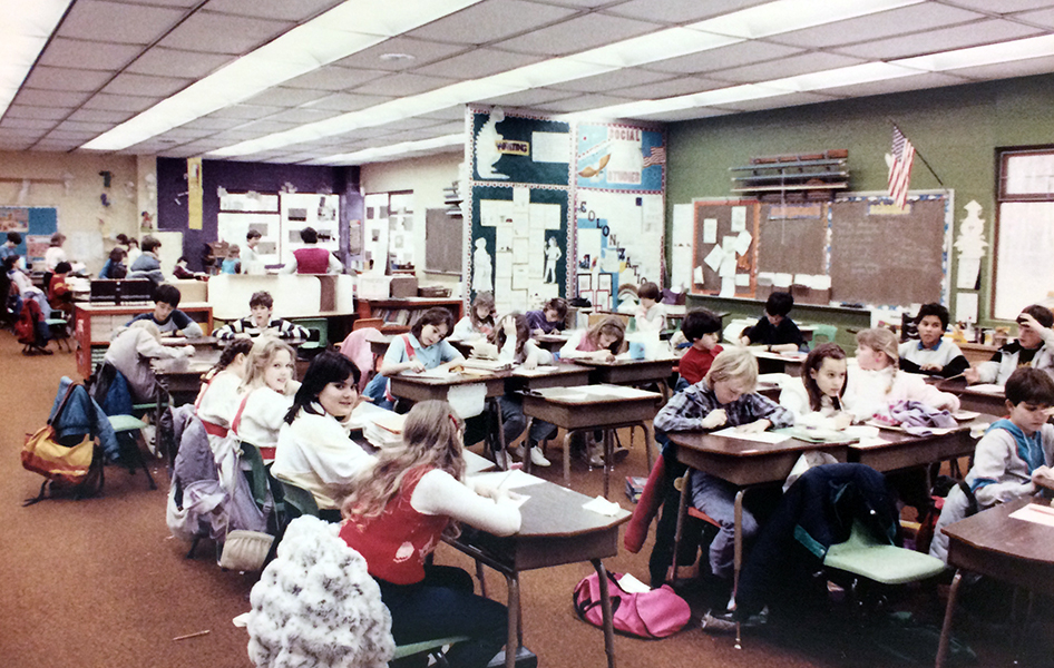 Color photograph of one of the open classrooms at Orange Hunt Elementary School. Individual desks have been clustered together in several, mostly linear, groupings of three or four children. The students in the foreground are working on one lesson, and in the distance a separate group of students can be seen working on a different lesson with another teacher.
