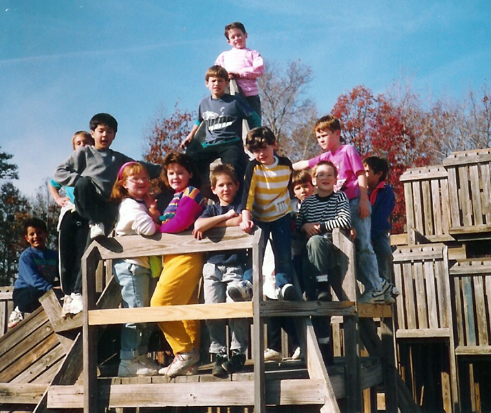 Color photograph of students posing on the wooden playground built in 1983. It is a crisp fall day. In the distance some trees have lost their leaves and others are bright red in color.