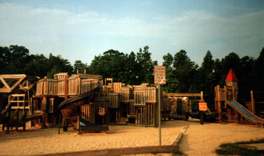 Color photograph of the playground that was built in 1983. It is a wooden structure with slides, ramps, turrets, and climbing structures.