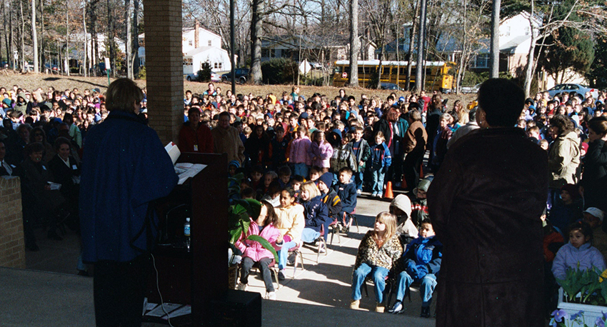Color photograph taken during the re-dedication ceremony. The photographer is standing near the front doors of our school looking out toward the bus loop. Principal Barbee can be seen standing at a podium addressing the entire student body and a large group of parents and community members who are gathered outside in front of the building to watch the ribbon cutting ceremony.