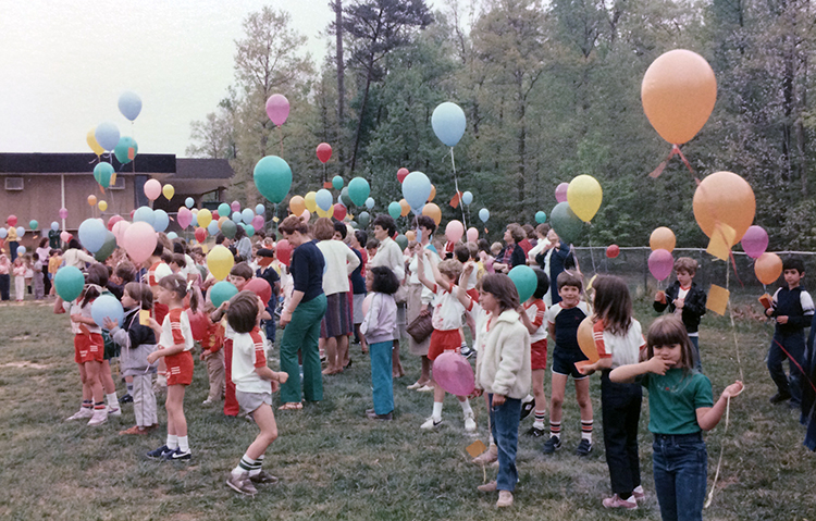 Color photograph of a large group of students and teachers outside Orange Hunt Elementary School on the playground field. The children hold colorful balloons that have small paper notes affixed to them by string. The children are waiting for the signal to release the balloons.