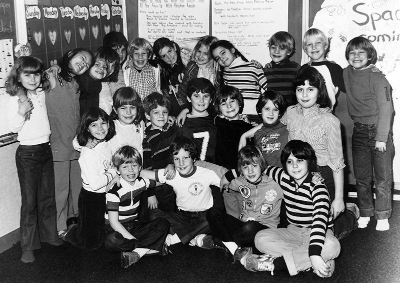 Black and white photograph of a large group of students posing for the camera. From the look of their clothing, the picture was likely taken during the late 1970s or early 1980s. 23 students are pictured, 10 of whom are girls. All the children are hugging and smiling, with their arms around one another. The photograph was taken in a classroom and there are handwritten lesson notes and a calendar on the wall behind them.