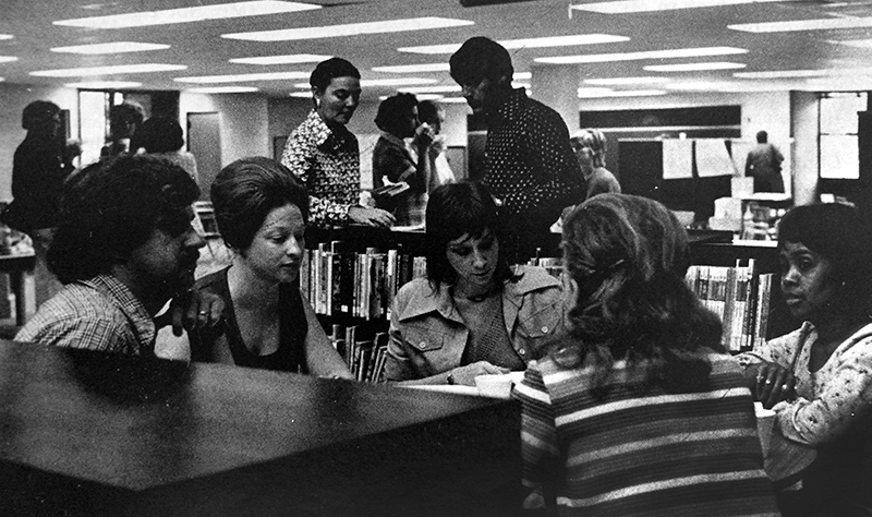Black and white photograph of several groups of teachers working together in the library at Lake Braddock Secondary School. In the foreground, a group of five teachers are seated close to one another and appear to be engaged in a discussion of some sort. The picture appeared in the November 1974 FCPS Bulletin publication.